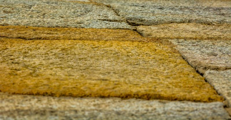 Beautiful texture made by paved tiles of a pathway near a park in Old fort, New Delhi, India. Beautiful sand tiles on side of a road royalty free stock image