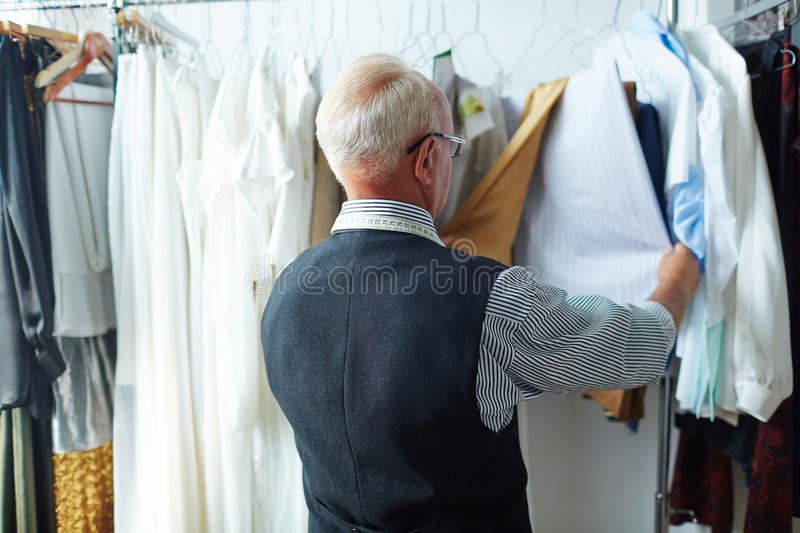 Old Fashioned Artisan Looking at Garments in Tailoring Studio. Back view portrait of old grey-haired tailor looking through custom made garments on hangers in royalty free stock image