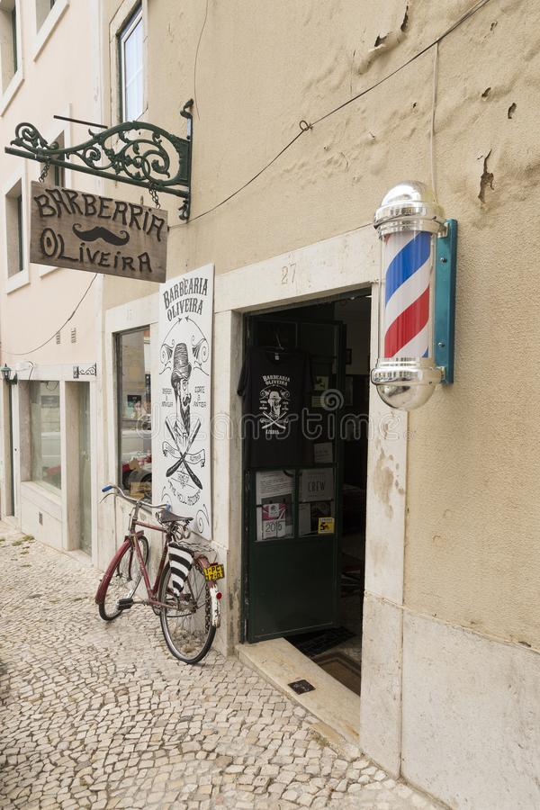 Old-fashioned barber shop with barber shop pole in Alfama sector, Lisbon stock photo