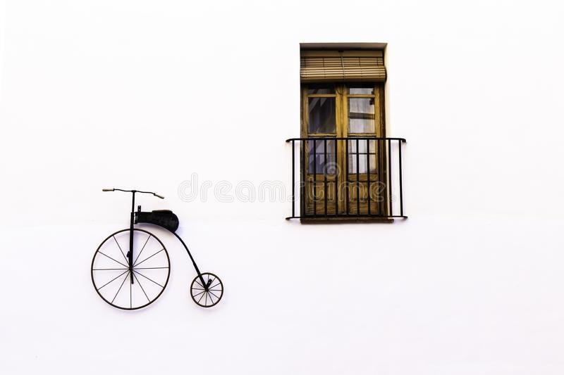 Old-fashioned bike and window with balcony as decor on a white wall. Copy space.  stock photo
