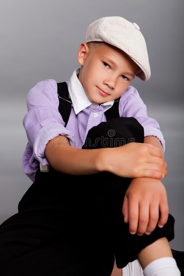 Old fashioned boy sitting on gray background stock images