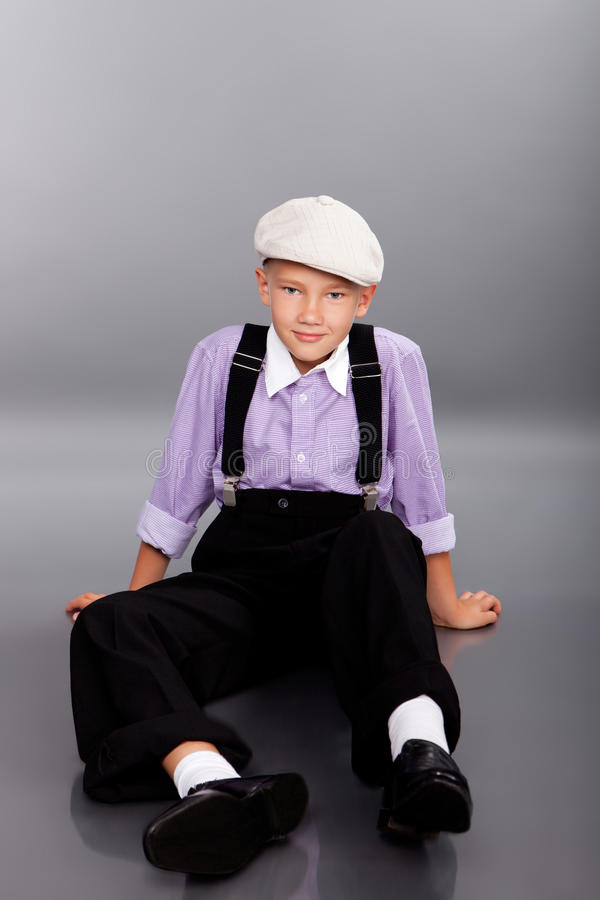 Old fashioned boy sitting on gray background royalty free stock images
