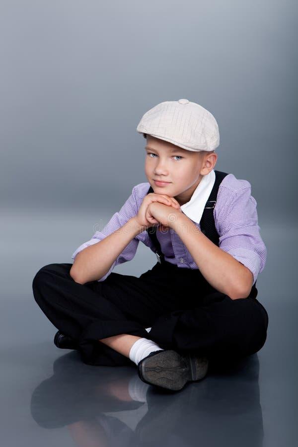 Old fashioned boy sitting stock image