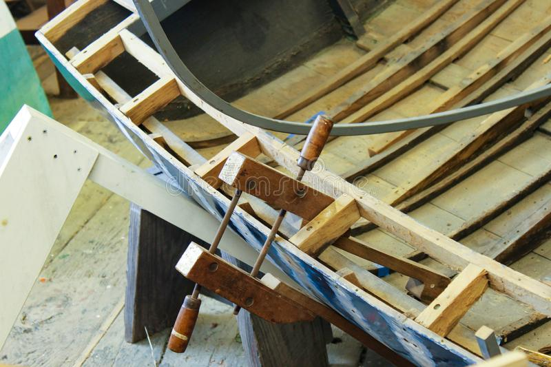 Old fashioned clamp holding curved wood being used to build a wooden boat royalty free stock images