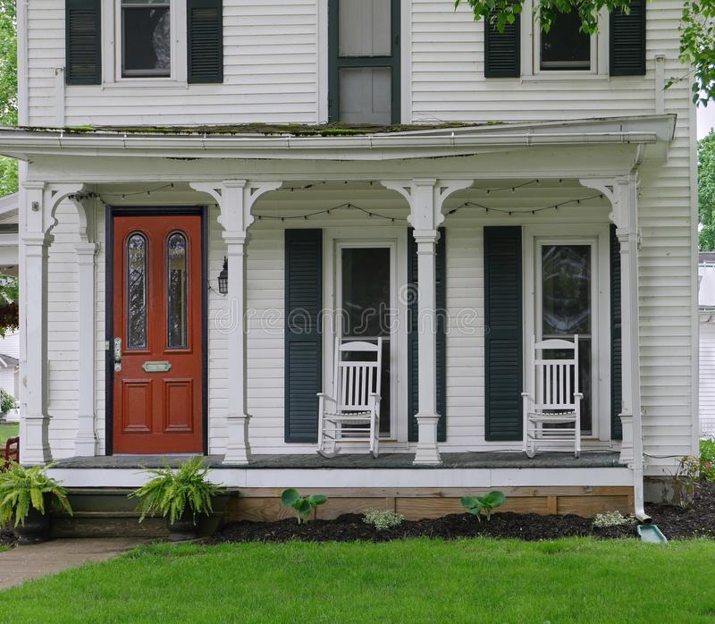 Clapboard house with large open porch and rocking chairs. Old fashioned clapboard house with large open porch and rocking chairs stock image