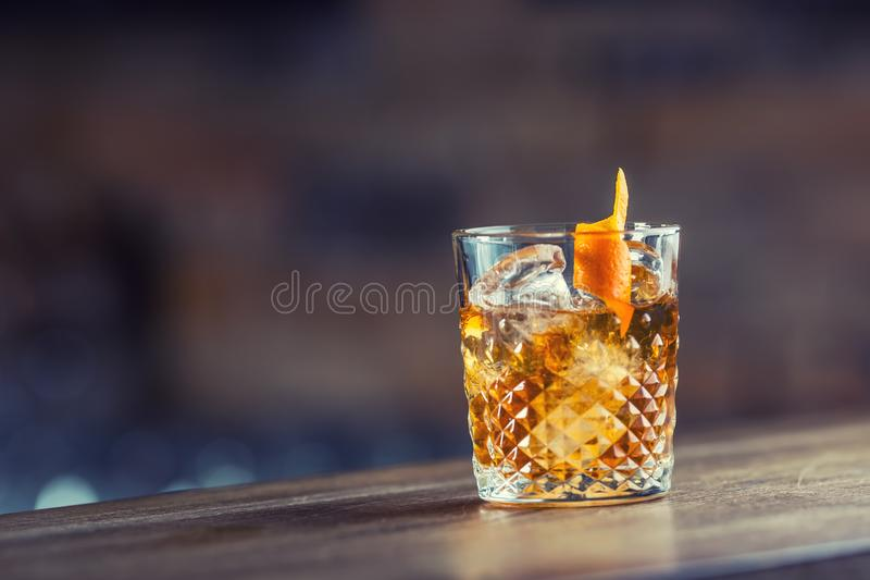 Old fashioned classic cocktail drink in crystal glass on bar counter. stock images