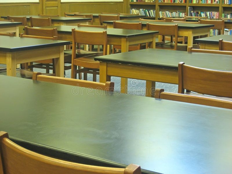 Old-fashioned Classroom. Wooden chairs and desks in old-fashioned classroom royalty free stock images