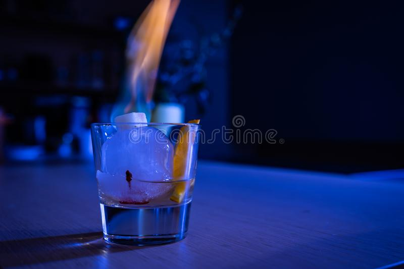Old Fashioned cocktail on ice ball with burning sugar royalty free stock photos