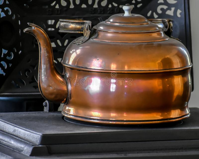 Copper Tea Kettle on Cast Iron Wood Stove stock image