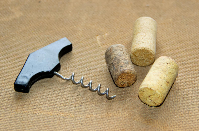 An old-fashioned corkscrew and three used corks on embossed surface. Selective focus royalty free stock image