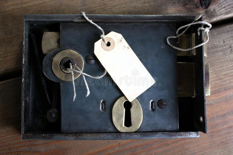 Old fashioned door lock and tag. Old fashined door lock and tag label on locksmith's workbench royalty free stock image