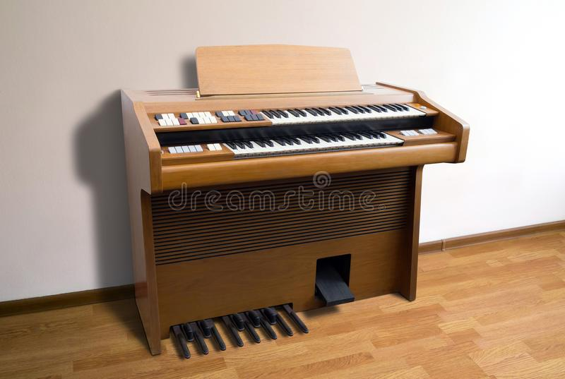 Vintage electric organ. Old-fashioned double-keyboard electric organ standing by a wall in a room royalty free stock image