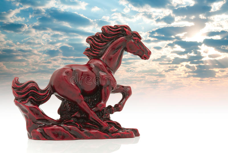 Old-fashioned figurine red horse on sky stock images