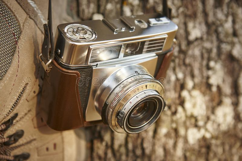 Old fashioned film camera detail and hiking boots. Travel. Background stock photography