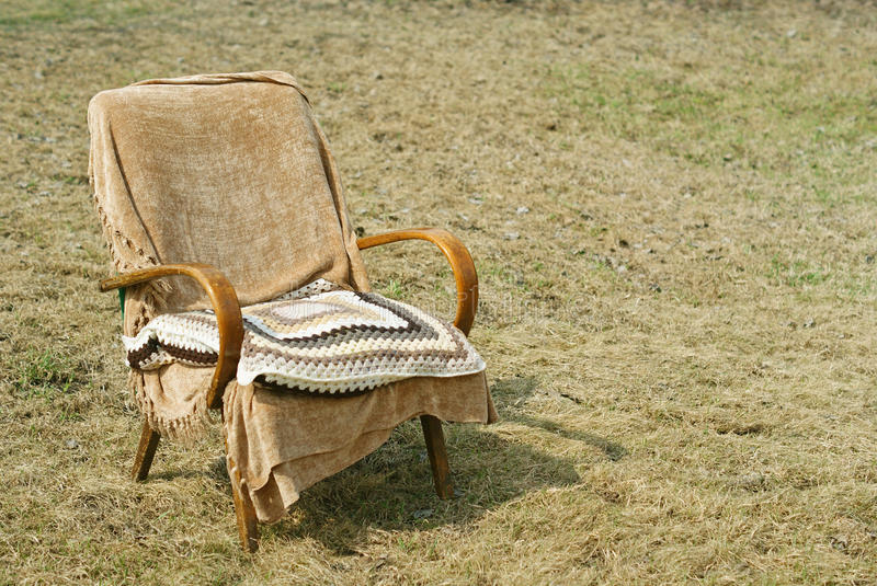 Old-fashioned garden chair and pillow. Old-fashined garden chair with a textile cover and wool pillow stock image