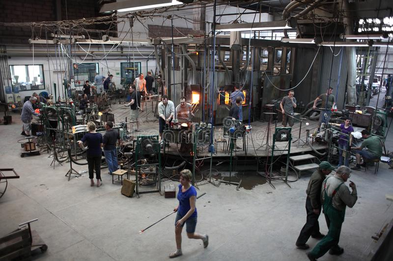 Old fashioned glass workshop. Factory floor in glassworks. Teamwork during traditional handmade glass production royalty free stock image