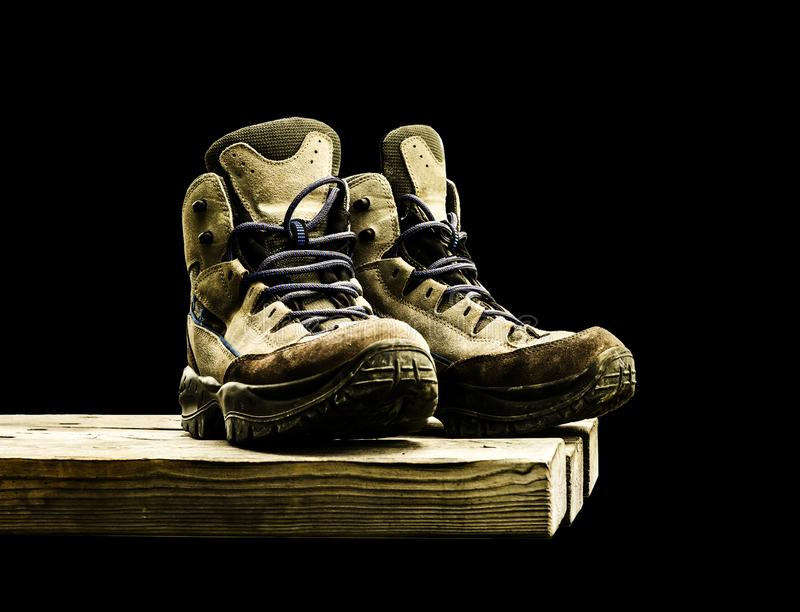 Old-fashioned hiking boots on wood. Isolated oh black background stock image