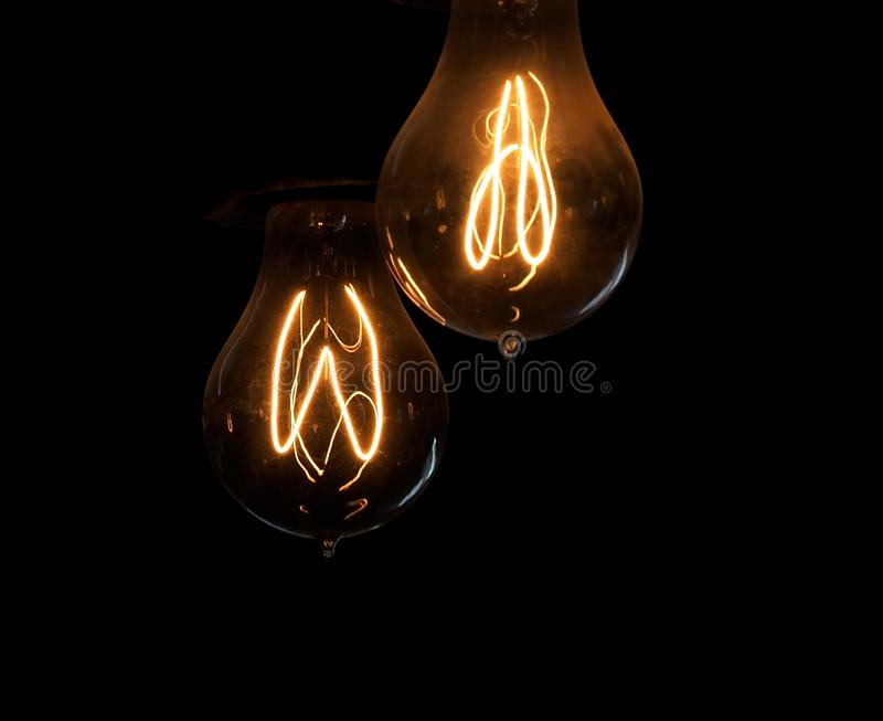 Incandescent Light Bulbs With Glowing Filament. Old fashioned incandescent light bulbs with glowing filament in dark room stock photos