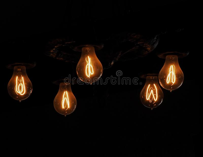 Incandescent Light Bulbs With Glowing Filament. Old fashioned incandescent light bulbs with glowing filament in dark room stock photography