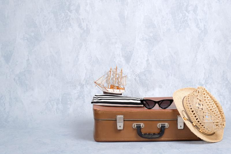 Old fashioned leather travel bag with summer marine accessories: glasses, straw beach hat, toy sailboat on grey background. Banner royalty free stock photo