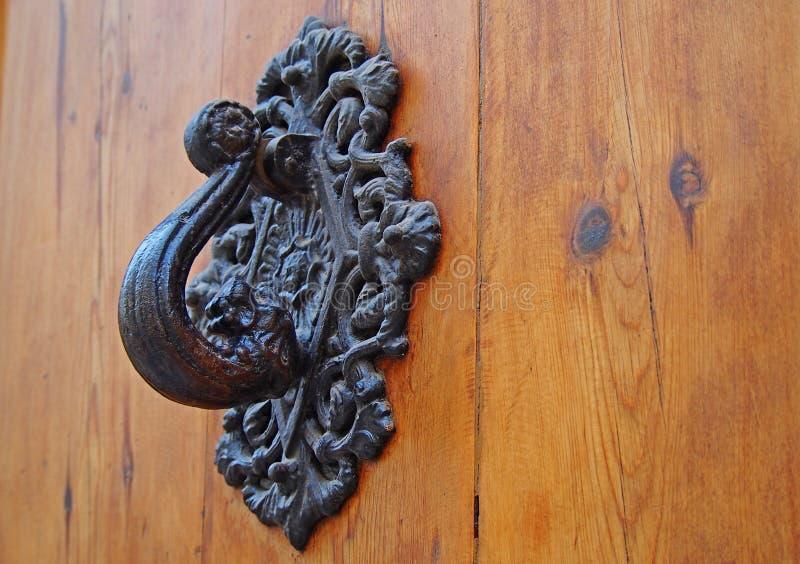 Old-fashioned metallic doorknob on a wooden door. Spain royalty free stock image