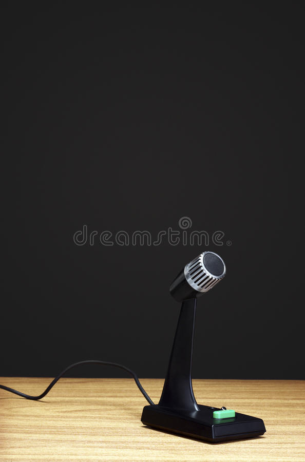 Old fashioned microphone on desk black background