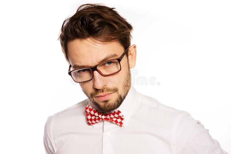 Old-fashioned nerdy businessman. Wearing a red and white polka dot bow tie looking over the top of his glasses , isolated on white royalty free stock images