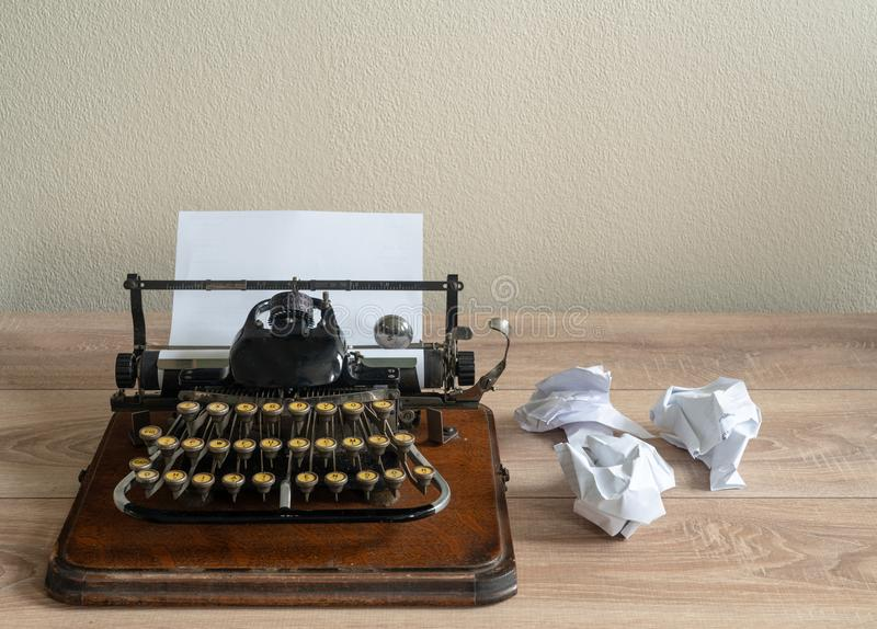 Old antique portable typewriter with screwed up paper on desk stock image