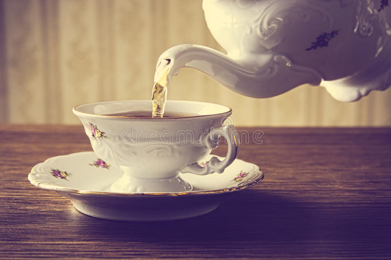 Old-fashioned pouring tea to cup on old wallpaper background. Old-style porcelain kettle pouring tea from jug to cup of tea on wallpaper background stock photo