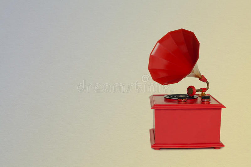 Old fashioned red gramophone, vintage paper background stock photos