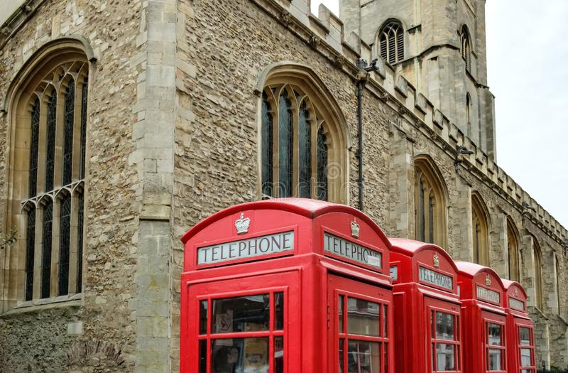 Old fashioned, red painted British phone boxes seen in front of a Cambridge church. The phone boxes are still in use and the detail of the door, glass and gold royalty free stock photos