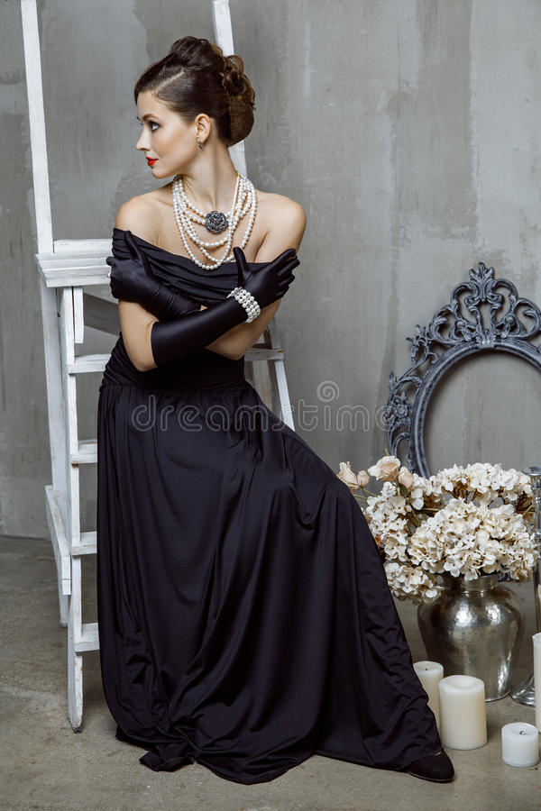 Old fashioned retro indoor fashion photography. Beautiful young fashion caucasian model in black long dress and fashion makeup and beautiful hairdo posing royalty free stock image