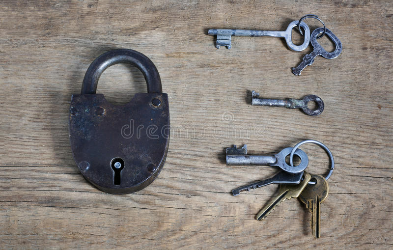 Old fashioned rusty lock with keys on wooden surface. Old fashioned rusty lock with three different pack of keys as deciding concepy on wooden surface royalty free stock photography