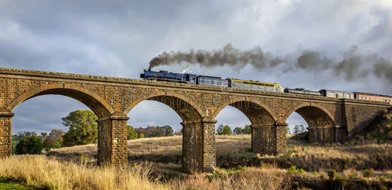 Old Fashioned Steam Train Crossing a Historic Bluestone Masonry Bridge, Malmsbury, Victoria, Australia, June 2019 royalty free stock photo