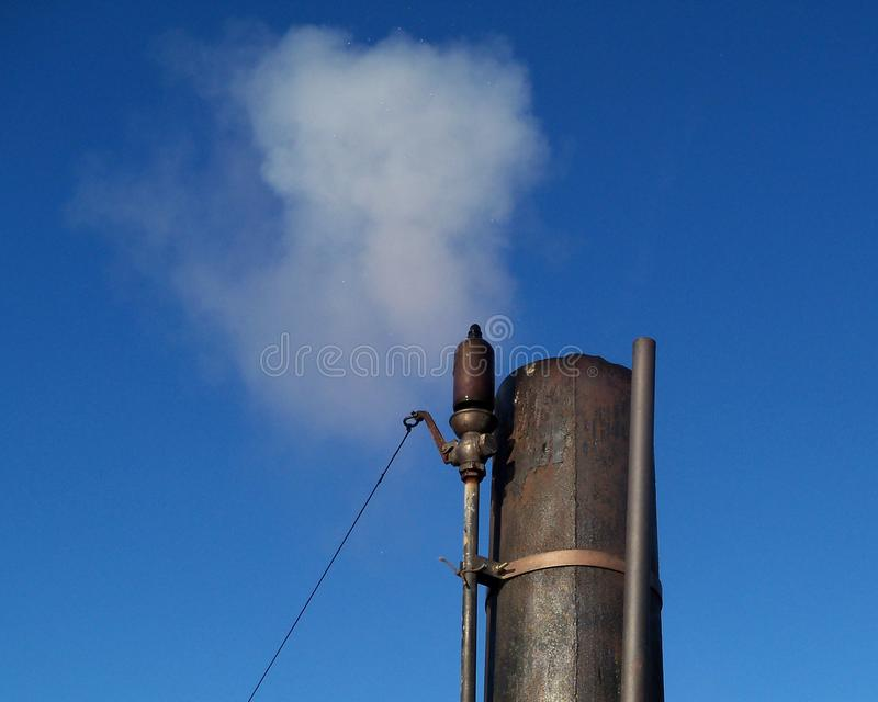 A old fashioned steam whistle. Blasts white steam into a bright blue sky royalty free stock photos