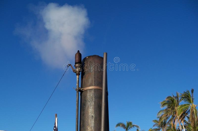A old fashioned steam whistle blows its top. A old fashioned steam whistle blasts white steam into a bright blue sky stock photos