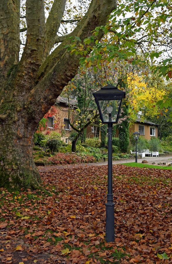 Old fashioned street lantern in Autumn in a park. Retro style street lantern in Autumn in a park setting, fall leaves on the ground, city park Stadtpark Lahr stock photo