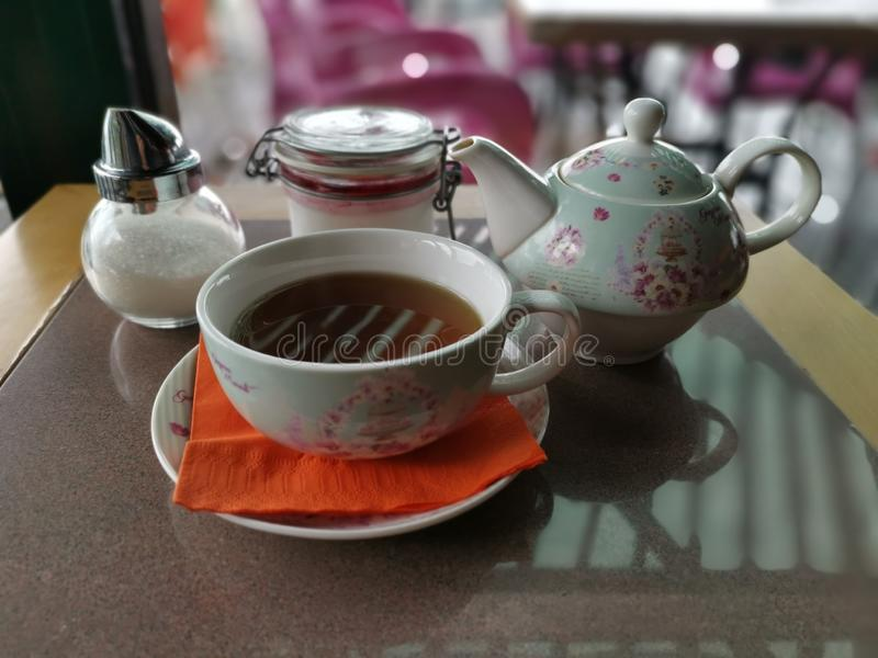 Old fashioned teapot with tea cup and sugar on table royalty free stock images