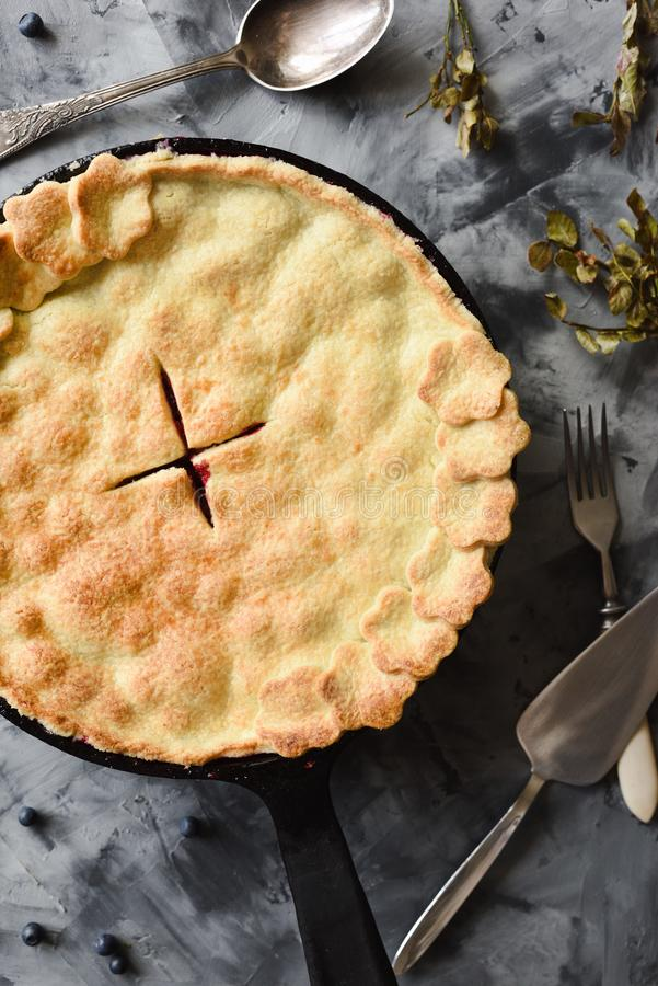 Old fashioned top crust berry pie on dark concrete background top view. Low key still life with natural lighting royalty free stock photography