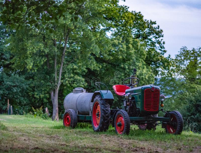 Old fashioned tractor sitting outside on grass stock photo