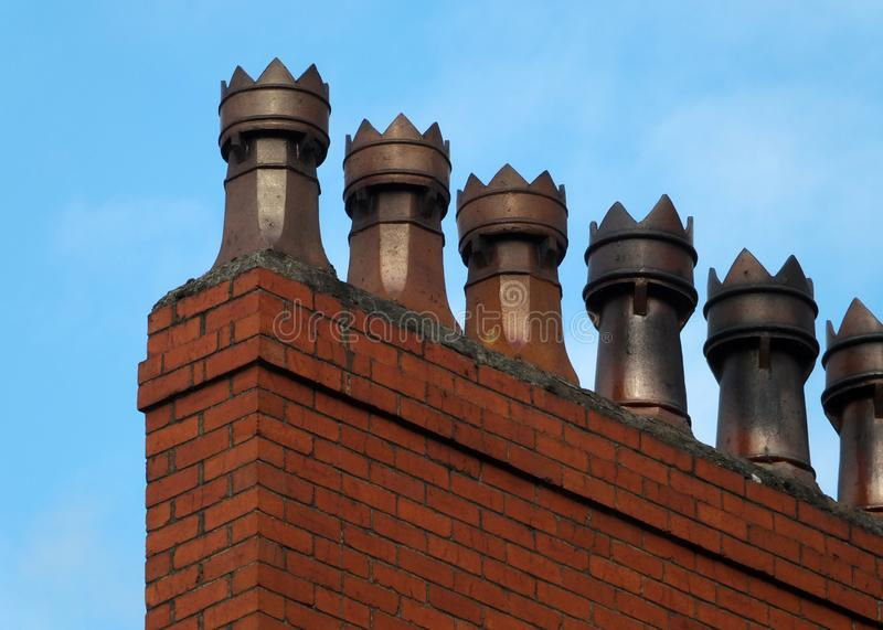 Old fashioned traditional clay chimney pots on a red brick support against a blue sky stock image