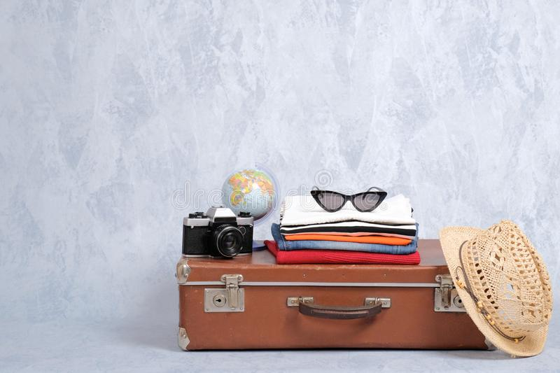 Old fashioned travel suitcase with summer accessories: glasses, pack of clothing, retro photo camera, straw beach hat on grey back. Ground. Banner mockup with stock images