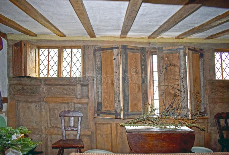 Old fashioned Tudor period room. A old fashioned room from the Tudor era the windows with small diamond shaped lead piping windows have wooden shutters on them stock images
