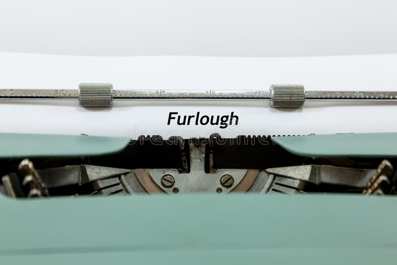 Furlough Concept - with old fashioned typewriter and paper with text. Old fashioned typewriter and paper - with typing that reads `Furlough stock photo