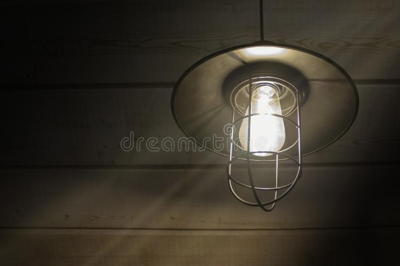 Old fashioned vintage lantern lamp burning with a soft glow light in an antique rustic country barn with aged wood wall royalty free stock photography