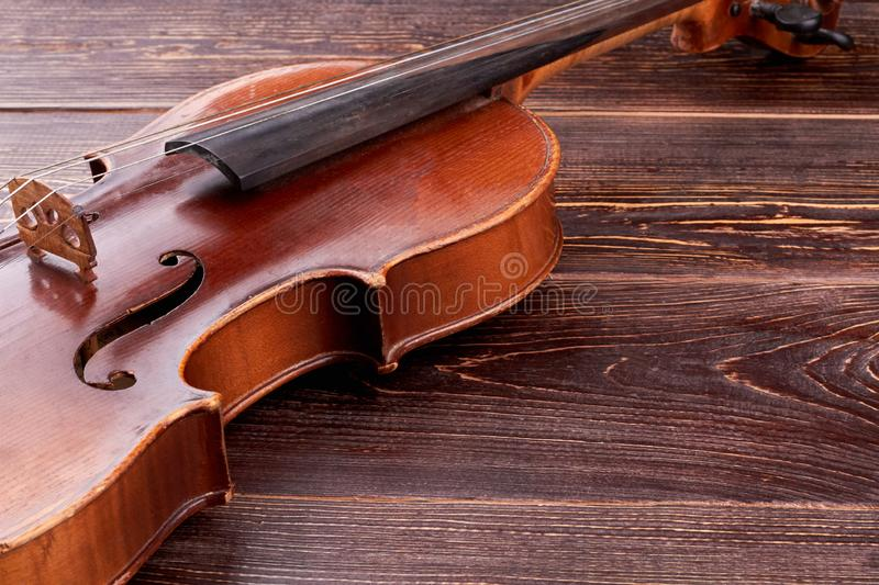 Old-fashioned violin on wooden background. Aged cello and copy space. Baroque style instrument royalty free stock images