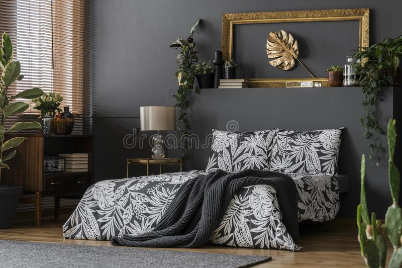 Old-fashioned cabinet in luxurious bedroom. An old-fashioned wooden cabinet and an elegant golden leaf in frame art in a dark gray luxurious bedroom interior royalty free stock photo