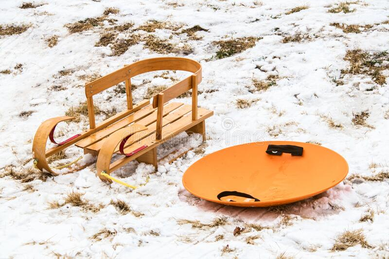 Old fashioned wooden sleigh and modern round orange plastic one sitting together in the snow royalty free stock photography