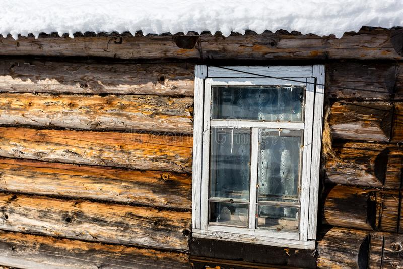Old- fashioned wooden window in winter, roof of the house covered with snow stock photography