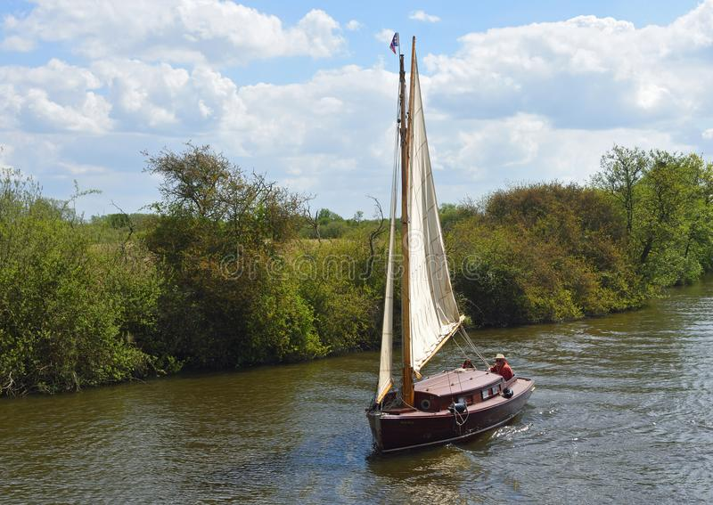 Old Fashioned Yacht under sail navigating the river Bure near Horning, the Norfolk Broads. royalty free stock images
